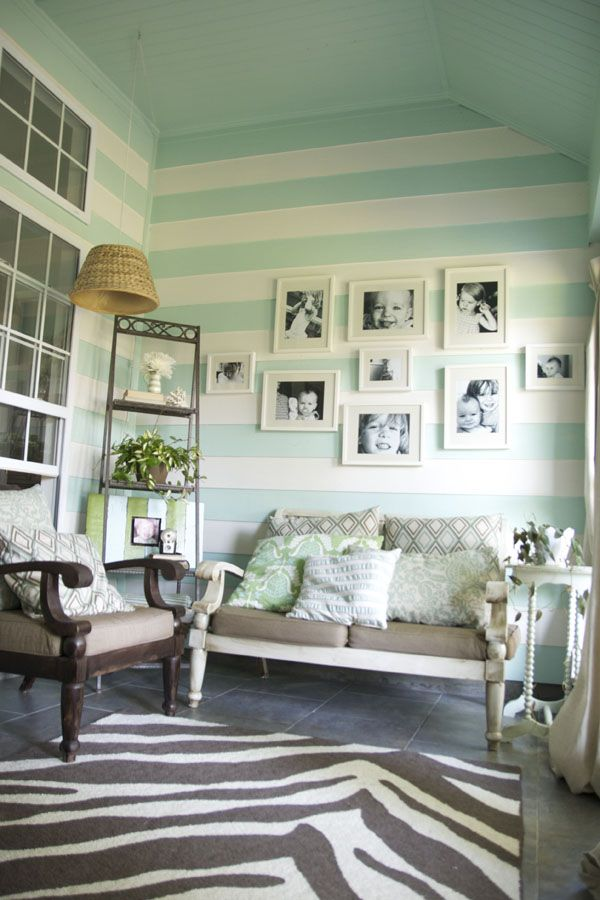 White and pale turquoise stripe, animal print rug, photos placed on the wall...    Love all of this.