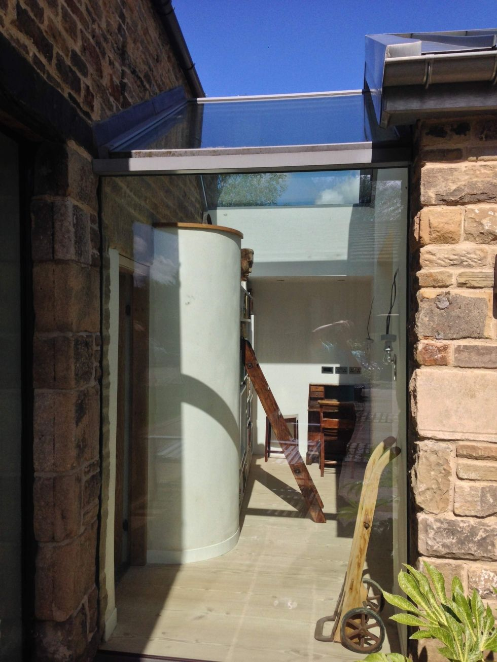 stone wall integrated with frameless glass door double glazed