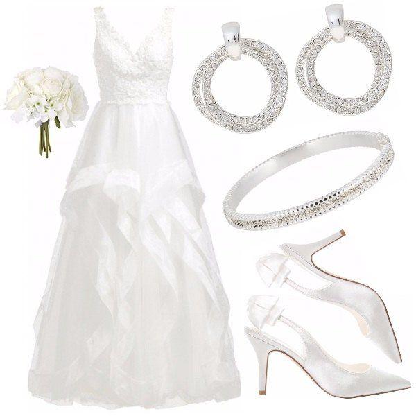 Per una sposa che vuole un look da vera principessa, senza rinunciare ad un tocco moderno. L'abito con bustino in pizzo e gonna asimmetrica è arricchito da accessori brillanti. Le scarpe, tacco 8, richiamano il tessuto lucido della gonna. Un bouquet minimal completa il look.