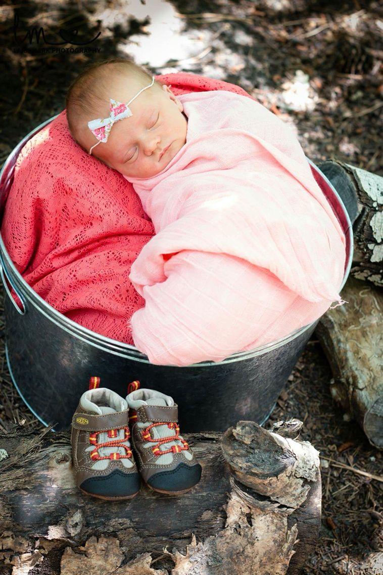 Newborn baby girl outside tin bucket
