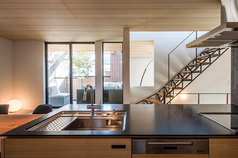 テラスに隣接したdkは開放感があり 光と風も心地いい 造作のキッチンは黒御影石の天板 板張りの天井は 照明の存在感をなくしてすっきりと キッチン ダイニング Idahomes 伊田工務店 アウトドアリビング 家 リビング