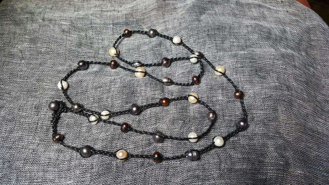Extra long pearl & leather necklace is a must have for your wardrobe. Whether worn in one long 50 inch strand or doubled as shorter necklace, this pearl and braided leather piece will complete your outfit.  Wear with jeans, suit or boho long skirts!  Don't miss this great necklace.