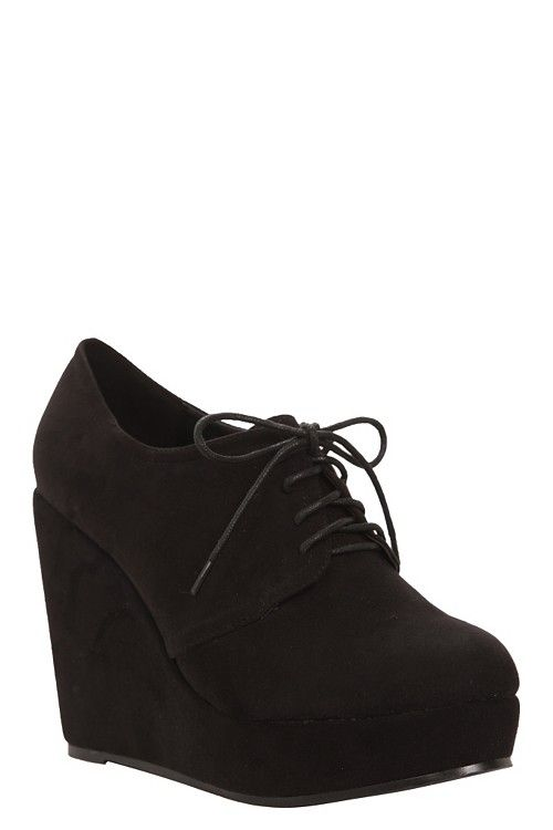 Inspired exclusive! Inspired by the classic Oxford, this luxe black suede bootie elevates style and, with sky-high wedges, your legs.