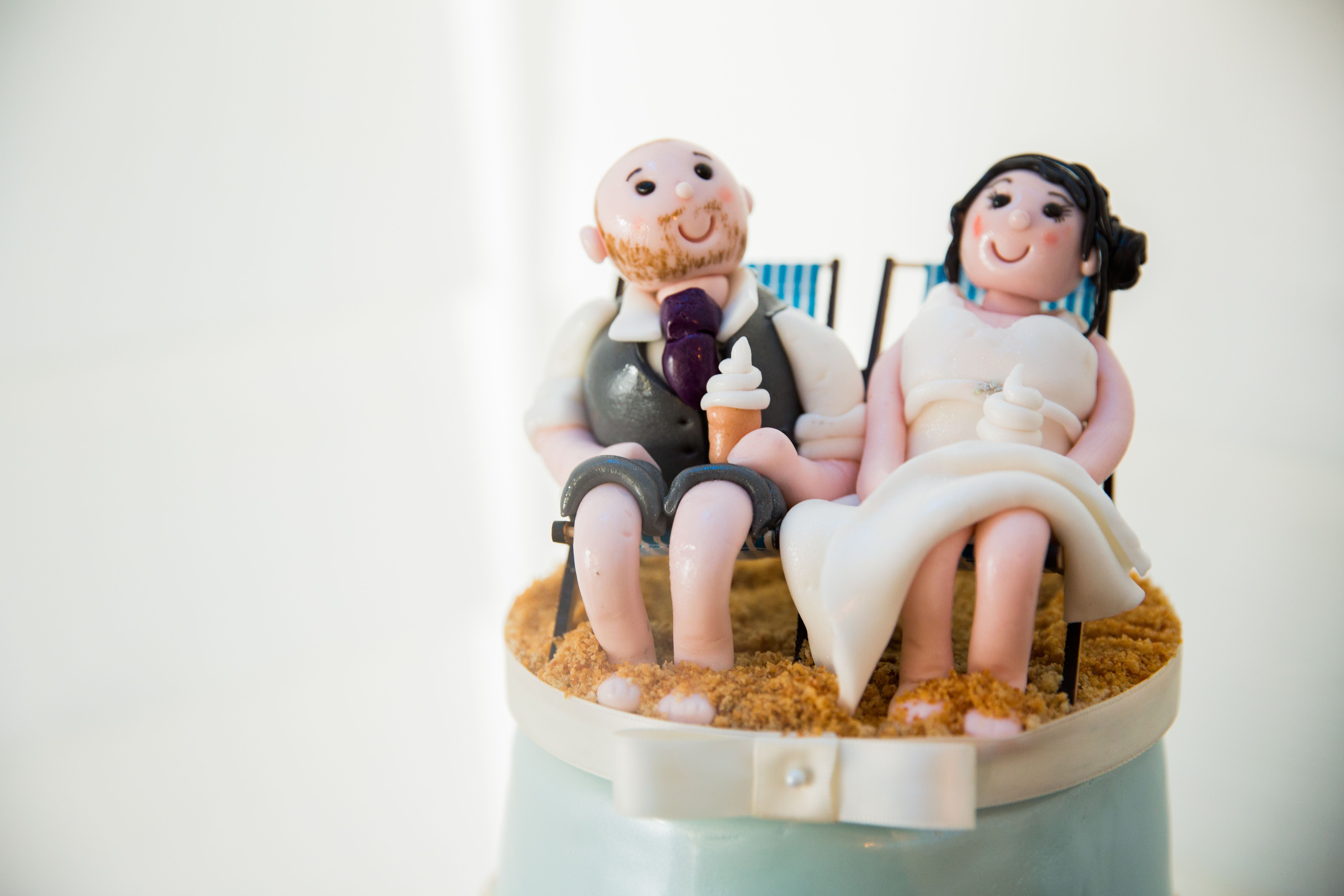 Wedding cake topper of bride and groom sitting on