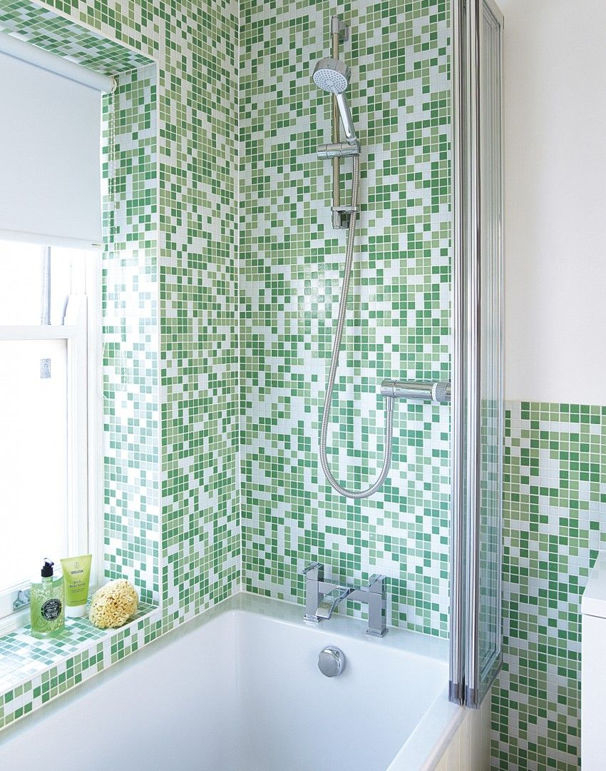 Green mosaic tiles transform this corner of the bathroom into a