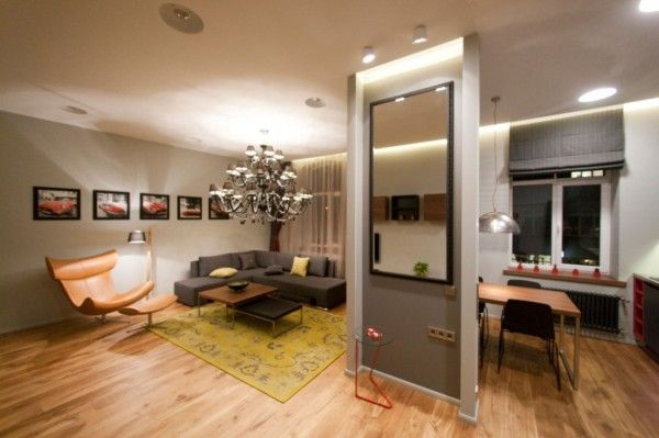 Apartment,Fascinating Studio Apartment Interior Design Ideas With Grey Wall And Laminated Wooden Flooring Featuring Room Divider And L Shaped Sofa And Combine With Small Kitchen And Big Chandeliers,Outstanding Studio Apartments Interior Designs