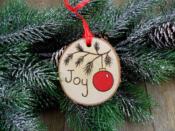 This wood burned birch slice ornament has the word Joy and a