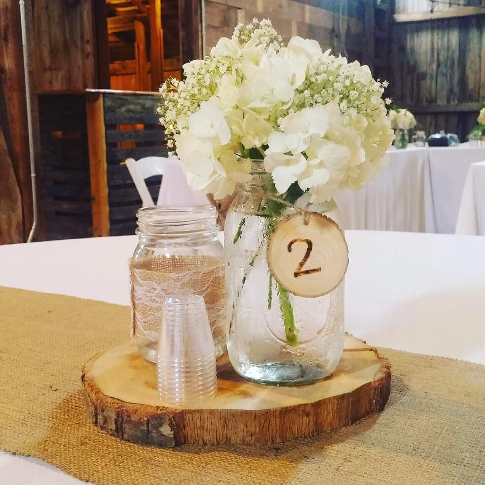 Mason Jar Centerpiece With White Hydrangeas Babies Breath On A Wood Slab Mason Jar Centerpieces Wood Slab Centerpiece Rustic Mason Jars