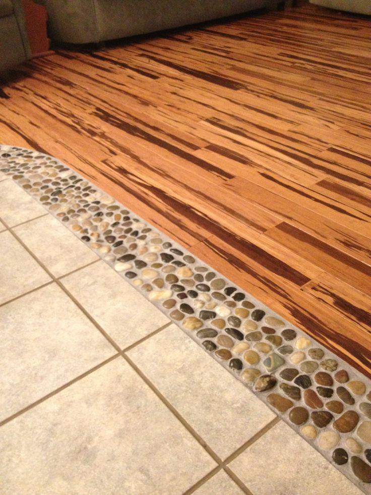 River rock in between wood and tile floors between the