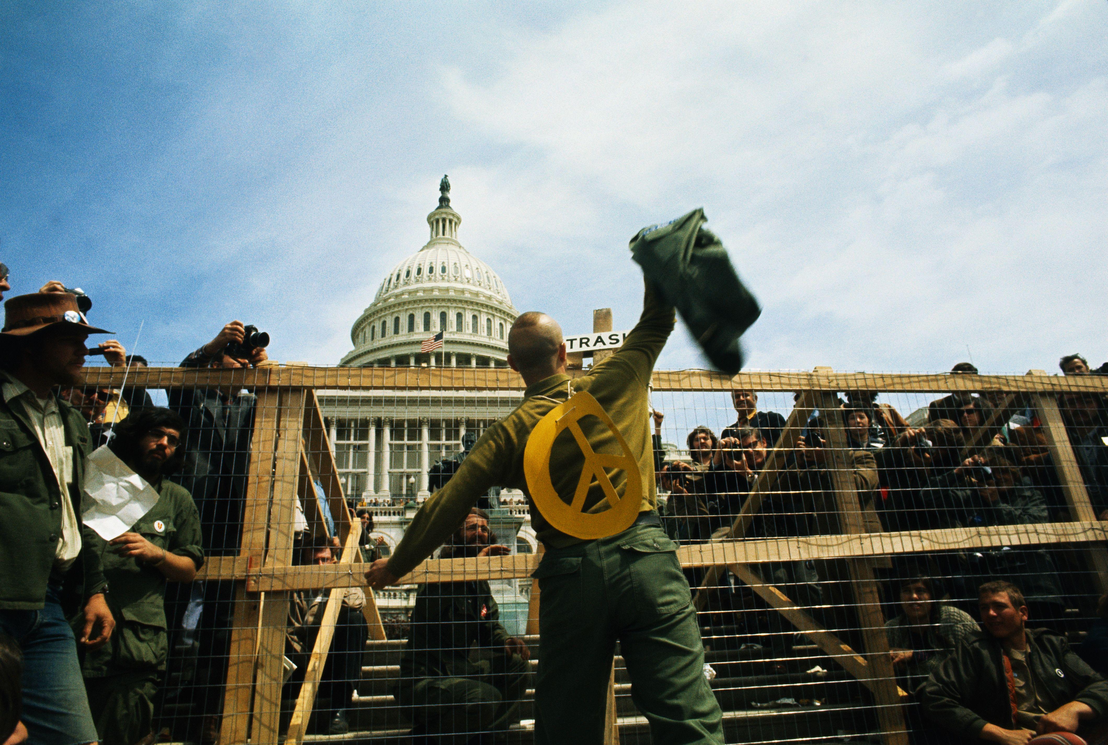 Protester Throwing Combat Jacket Over Fence Vietnam Anti War Protests Pictures Vietnam War History History Com Vietnam War Vietnam Protests Vietnam