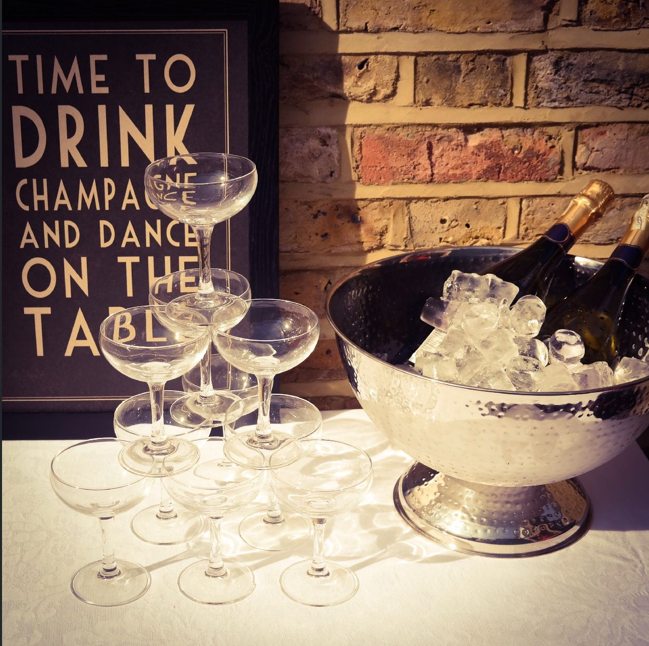 Champagne coupe tower, champagne ice bowl and framed 'Time to drink champagne and dance on the table' print. All from our prop collection and available for hire.