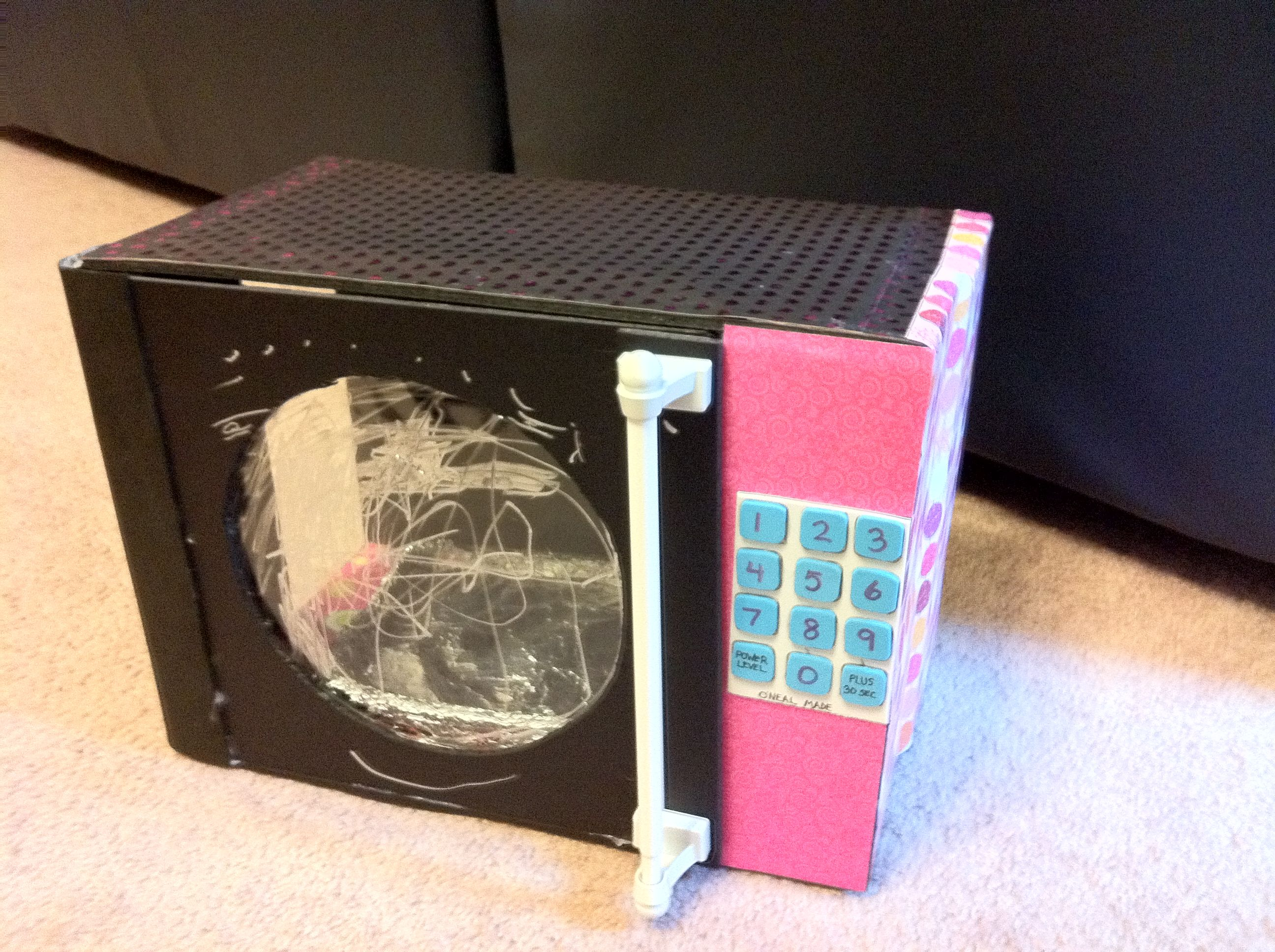 Microwave from foam board, scrapbook paper, curtain rod, and hot glue gun. Left side has an opening so the microwave can be turned on its side and used as a microwave oven.
