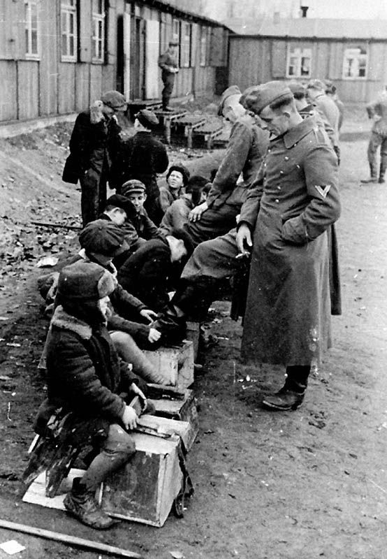 Soviet children clean the boots of German soldiers. Bialystok, Belarus. November 1942.