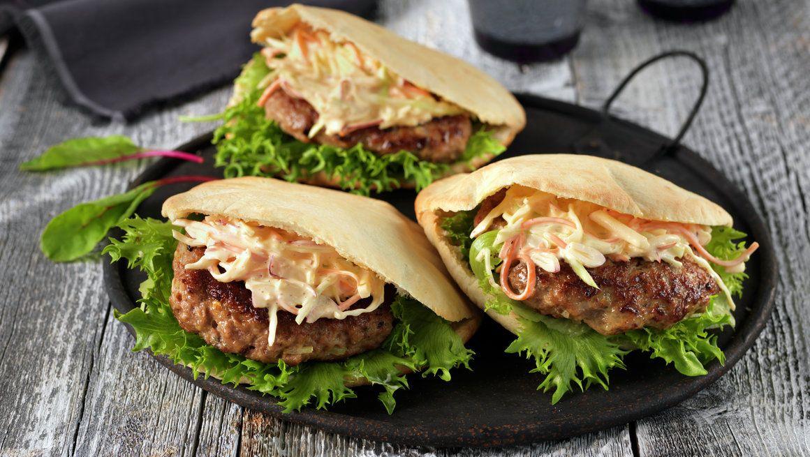 INGREDIENSER    6 PORSJONER Lammeburger: 1 kg kjøttdeig av lam 1 stk løk 2 båter hvitløk 2 ss spisskummenfrø 1 ts kvernet pepper 1⁄2 stk sitron 2 ts salt 1 ss frisk mynte (kan sløyfes) 1 dl melk 2 ss olivenolje 6 stk pitabrød 1⁄2 potte frisk koriander (kan sløyfes) 6 blader crispisalat Coleslaw: 1⁄4 stk hodekål 1 stk gulrot 1 stk rødløk 2 stk eple 11⁄2 dl majones 1⁄2 dl rømme 1 ss sitronsaft 1 ss sriracha (asiatisk chilisaus) 1⁄2 ts salt   SLIK GJØR DU  Ha lammekjøttdeigen i en bolle…