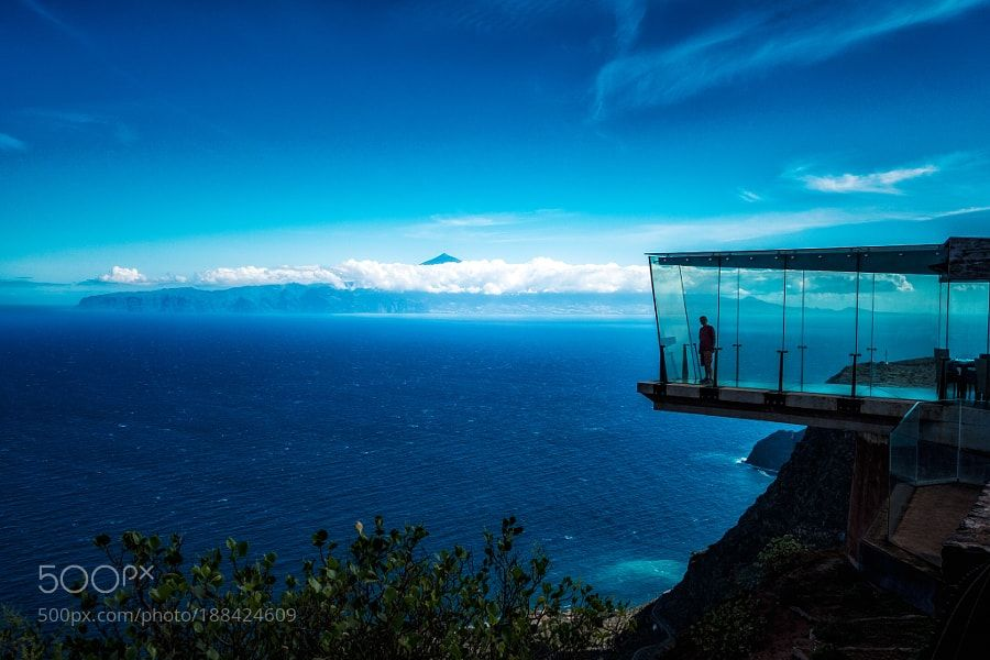 http://500px.com/photo/188424609 Skywalker by GittiStory -My husband hardly dared to step on this glass floor ;) It was indeed such a special feeling and you had to bring up all your courage.  Mirador de Abrante is a 7 m long glass-floored viewpoint in the North of La Gomera overlooking the Atlantic Ocean with exceptional views of Agulo and Mount Teide in Tenerife - a spectacle for the senses.  It is an architectural masterpiece a projection of glass designed by the architect José Luis…
