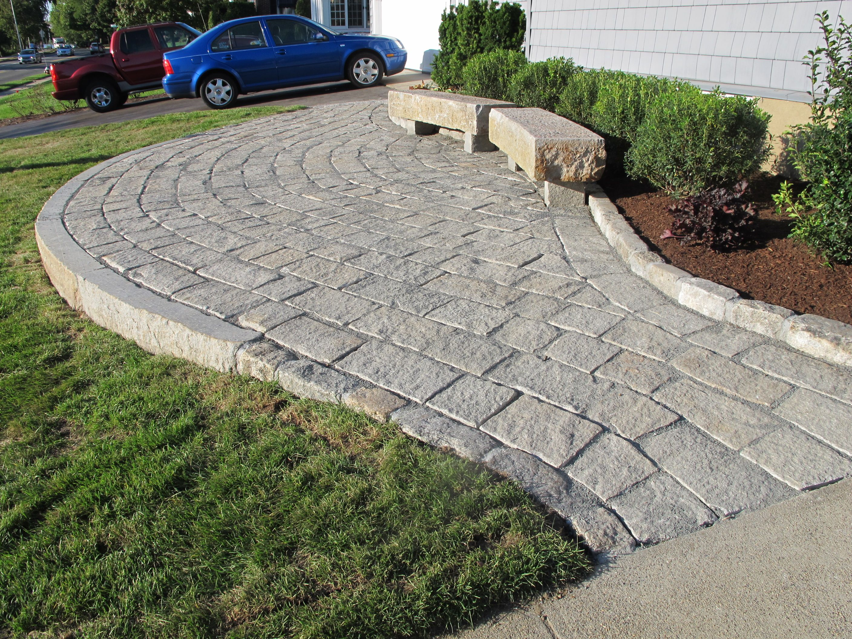 The Project Features A Raised Patio/walkway, Two Radius Benches,  Cobblestone Edging Along