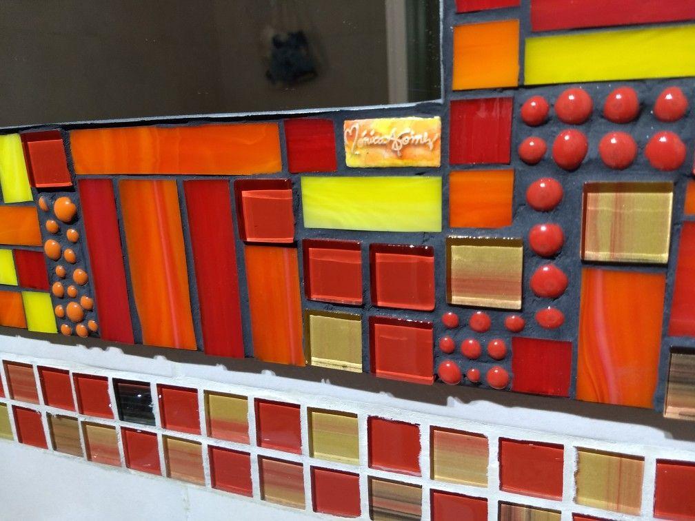 Espejo con marco hecho en vidrios rojos, naranja s y amarillos ...