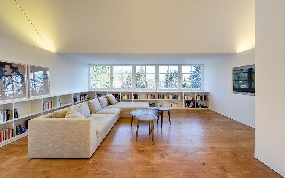 Individuelle küche im modern wohnbereich mit homogener holzfuboden neben halbhohe bcherregale zusammen mit deckenbeleuchtung und vaulted