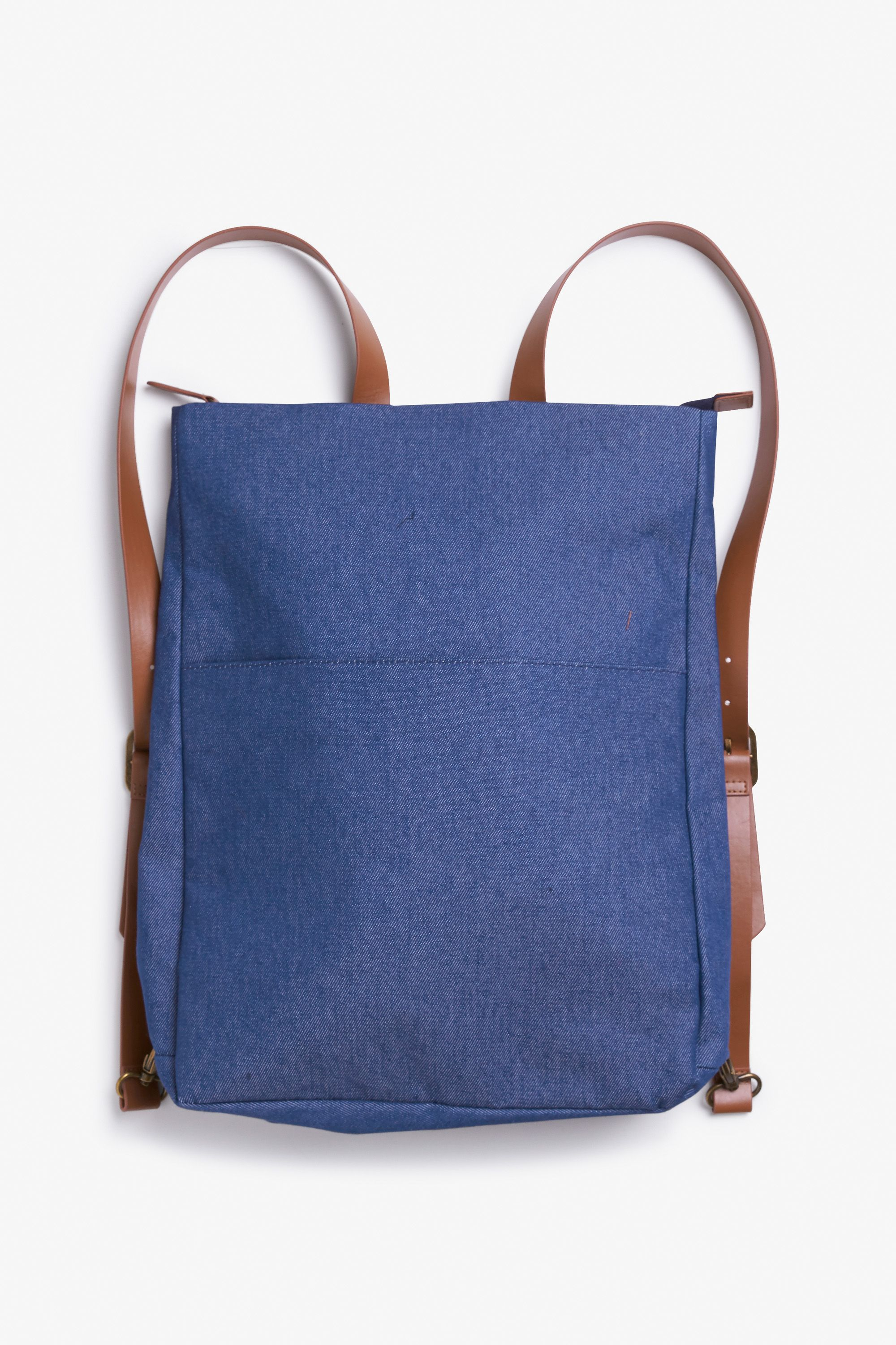 Asuper simplified denim backpack, which lies flat like a tote with a brass-coloured zipper straight across the top.