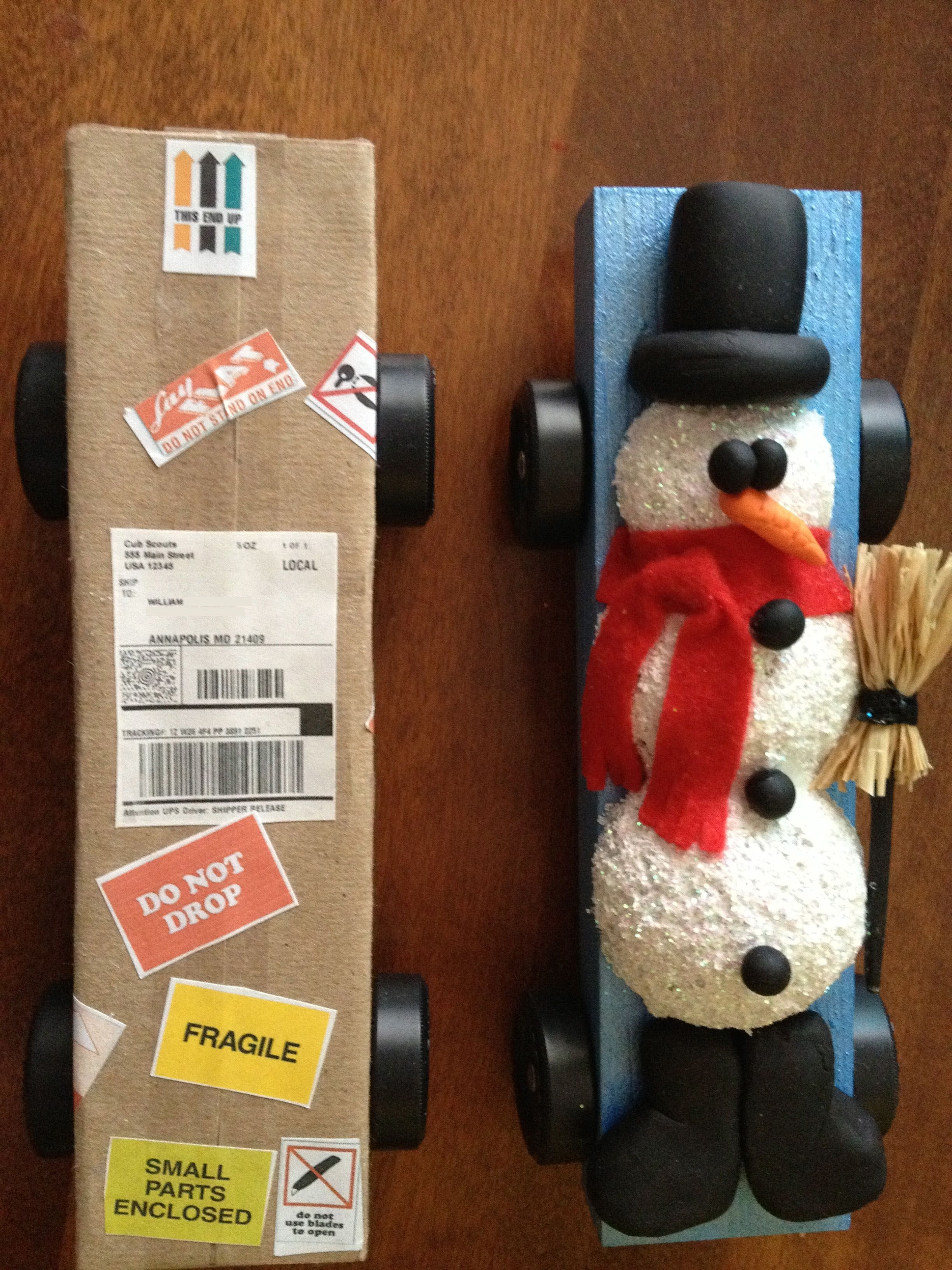 Packing box.  Shrunk preexisting labels in photoshop including UPS label which I edited with our address (which I blacked out for this post!)  Snowman is halved styrofoam balls, texture paint, glitter and Sculpey for features hat and boots.  Scrap felt scarf.  Raffia broom tied onto portion of painted skewer with floss.