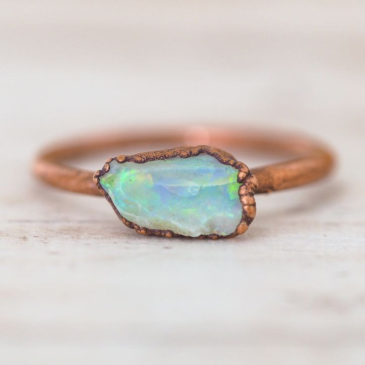 Australian Raw Opal and Copper Ring is part of Raw gemstone jewelry, Raw opal engagement ring, Natural opal jewelry, Copper rings engagement, Minimalist jewelry, Unique jewelry - Beautifully handcrafted using the most stunning handpicked Australian Raw Opals  Each design is unique, creating its own personality and originality    The colour and shape of the Raw Opal will never be the same, each varying in shape and colour, making it that perfect special piece you have been looking for! The opal stone enhances imagination and creativity, decreases confusion    Each of our copper jewels is recycled whereby they are crafted out of copper material that has been loved before it became a beautiful Indie and Harper piece!