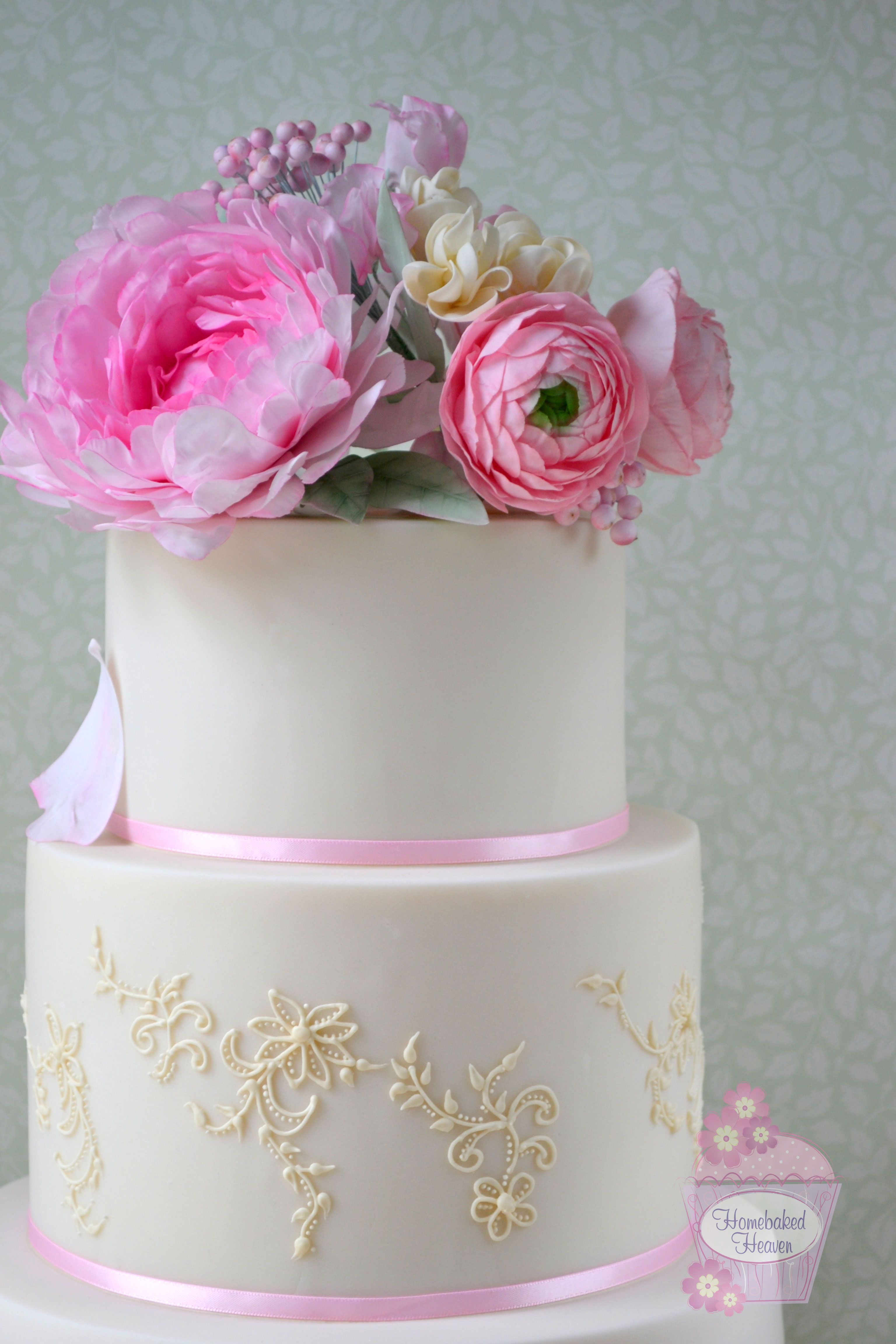"""Wedding cake decorated with sugar peony, ranunculus, snowberries, sweet peas and stocks.  Royal icing piping inspired by bride's Romantica of Devon """"Olympia"""" wedding dress."""