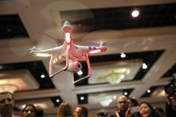 A DJI Innovations Phantom remote-controlled drone hovers above the CES press event.