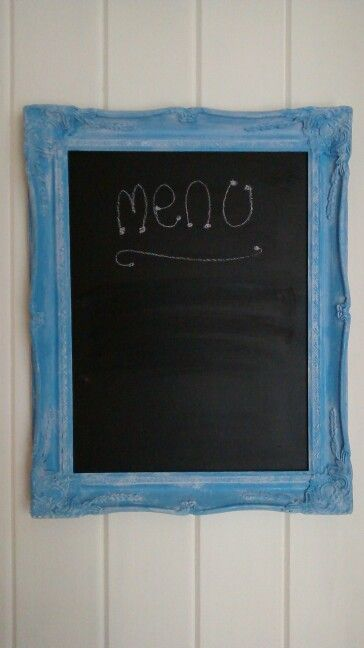 An old gold picture frame spray painted blue, aged and distressed by dry brushing with white, middle painted with chalk board paint.
