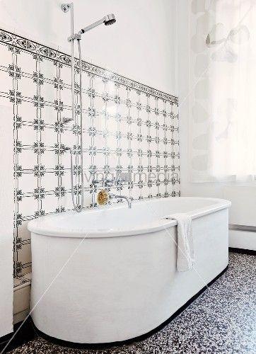Weisse, Freistehende Badewanne Auf Terrazzoboden, An Wand Fliesen Mit  Schwarz Weissem Vintage Muster