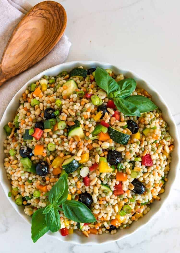 This easy to make Israeli couscous salad has fresh colored bell peppers, green onion, tomatoes, zucchini, olives and basil tossed in a simple lemon dressing