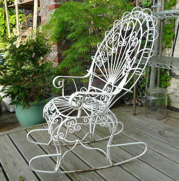 Petite, Wrought Iron Outdoor Rocking Chair With Peacock Fan Back.