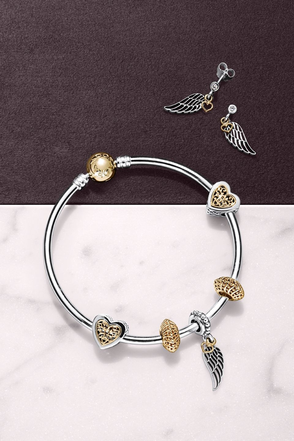 61f953c96c5 PANDORA's filigree angel wing charm and earrings with dangling 14k gold  hearts are the perfect present to represent love and guidance.