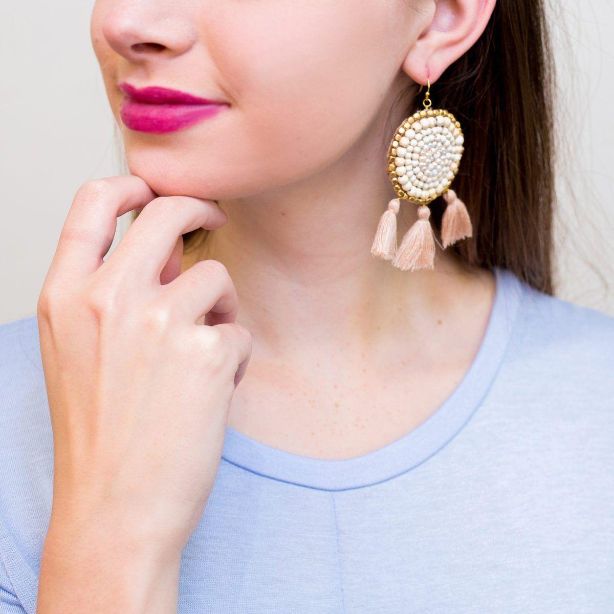 7d77d34639b51 closeup of model wearing white howlite beaded circle tassel earrings ...