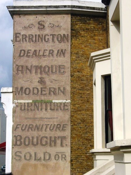 Faded hand-painted lettering on a wall (ghostsign) for S Errington furniture dealer