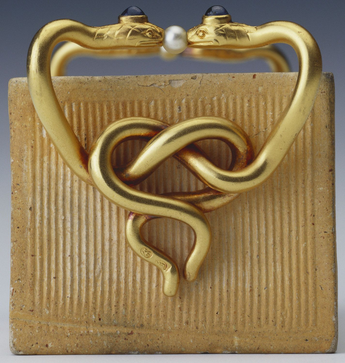 One of three match holders formed of bricks made by the Gusareva factory in Moscow and now in the Royal Collection, two of which are by Fabergé. This example by Fabergé is mounted with gold handles in the form of pairs of entwined serpents decorated with sapphires and pearls; workmaster Erik Kollin, before 1896. Acquired by King Edward VII, date unknown.