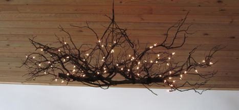 This is a large ceiling mounted light fixture made from manzanita branches that were lashed together with natural twine and wrapped with salvaged christmas lights.