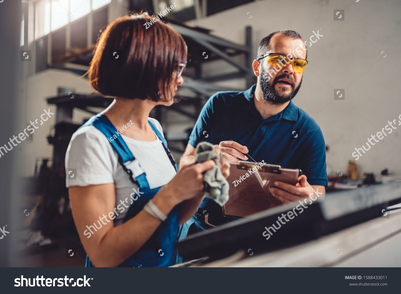 Factory supervisor counseling female CNC machine operator