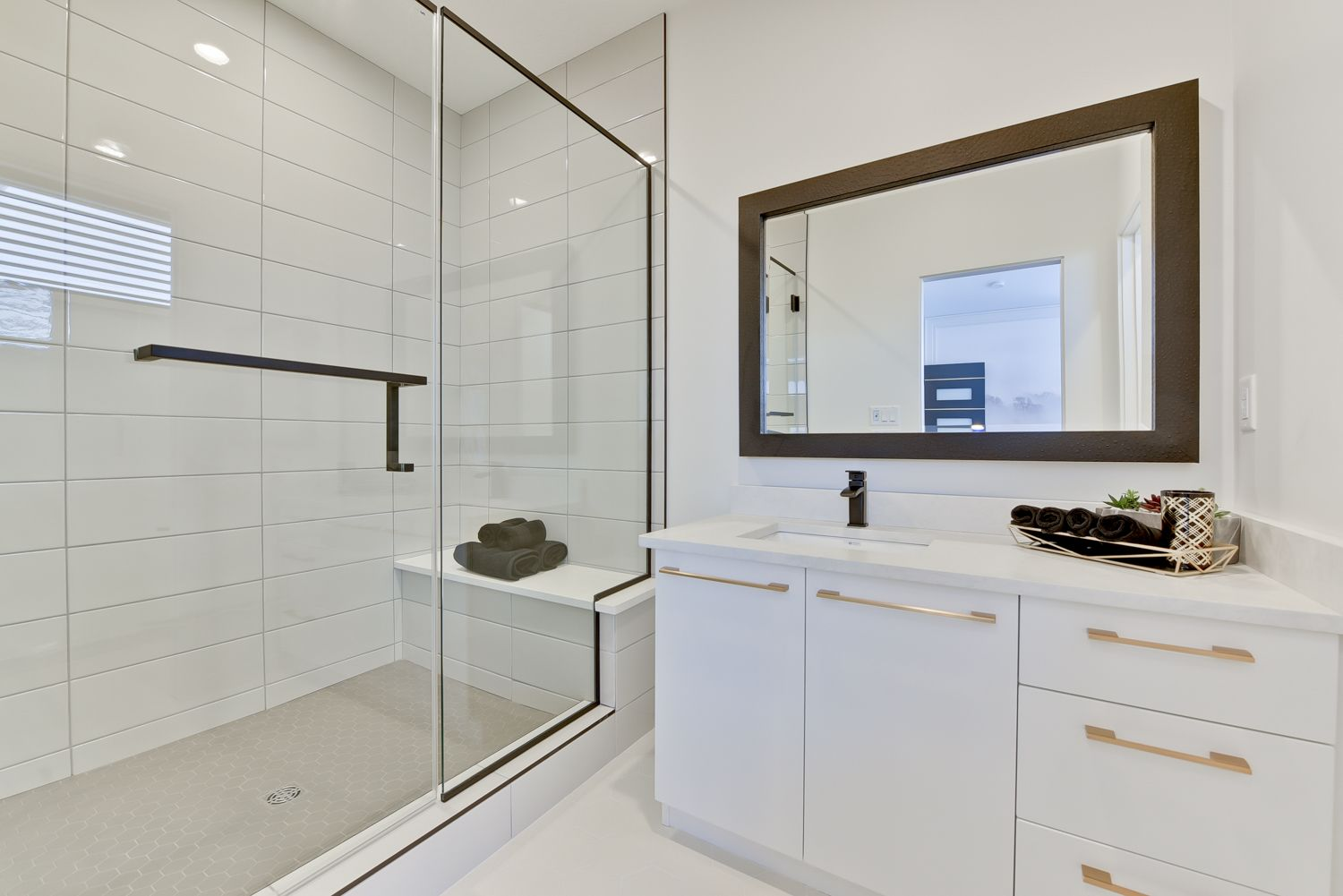 Walk in shower with glass door in bathroom with large white tiles ...