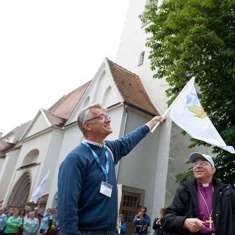"""LWF General Secretary, Rev. Dr Martin Junge and President, Bishop Dr Munib Younan wave a """"Liberated by God's Grace"""" flag during the Pilgrimage in Wittenberg.  #Day200 until the Twelfth Assembly. #Assembly365 #LWFAssembly"""