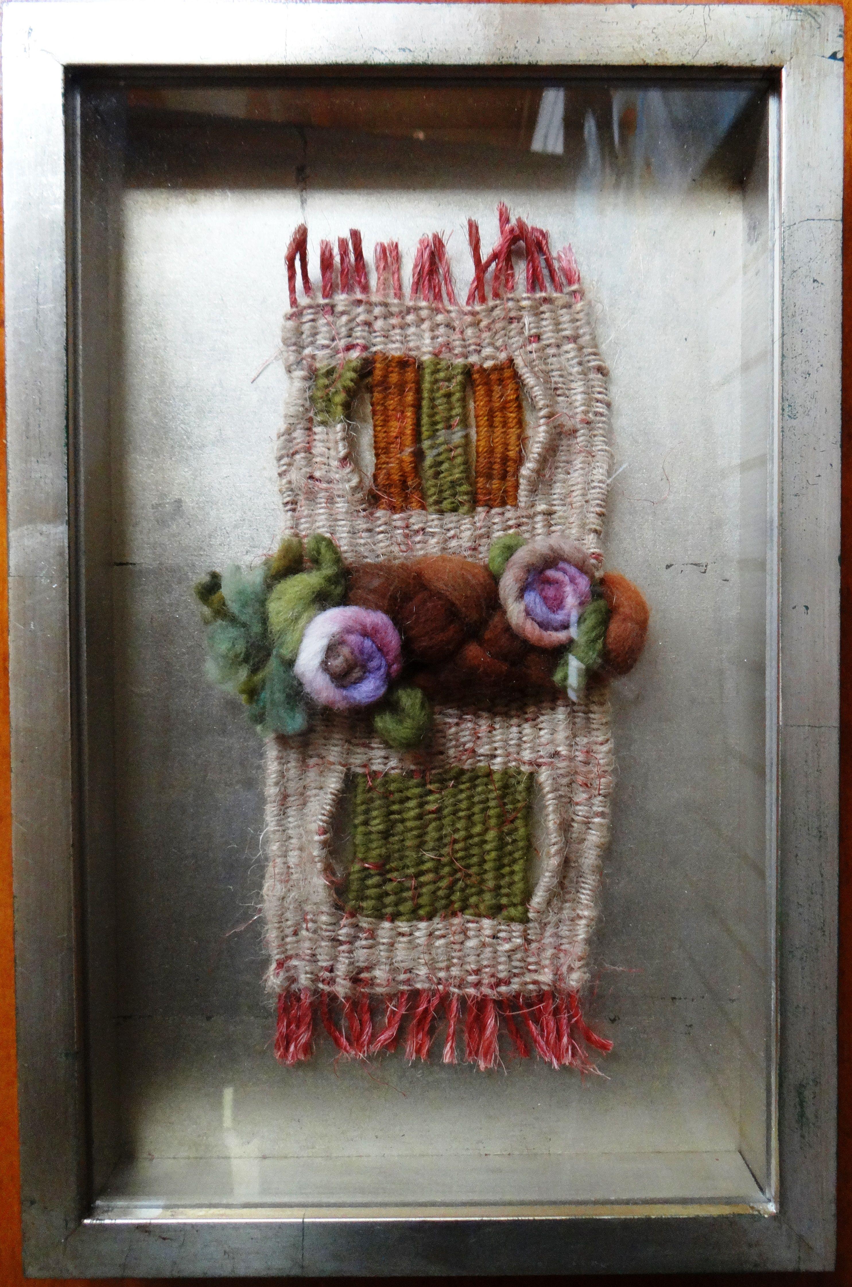 Textil a telar, marco madera con lámina de plata, cubierta de vidrio. 40 cms x 26 cms
