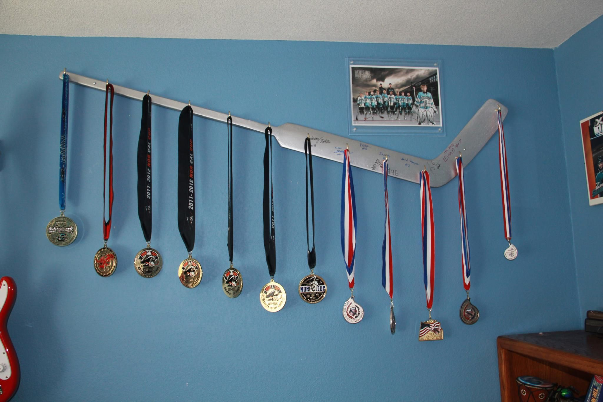 Clever way to hang medals. Could do this with lots of sports. Baseball bat, etc.