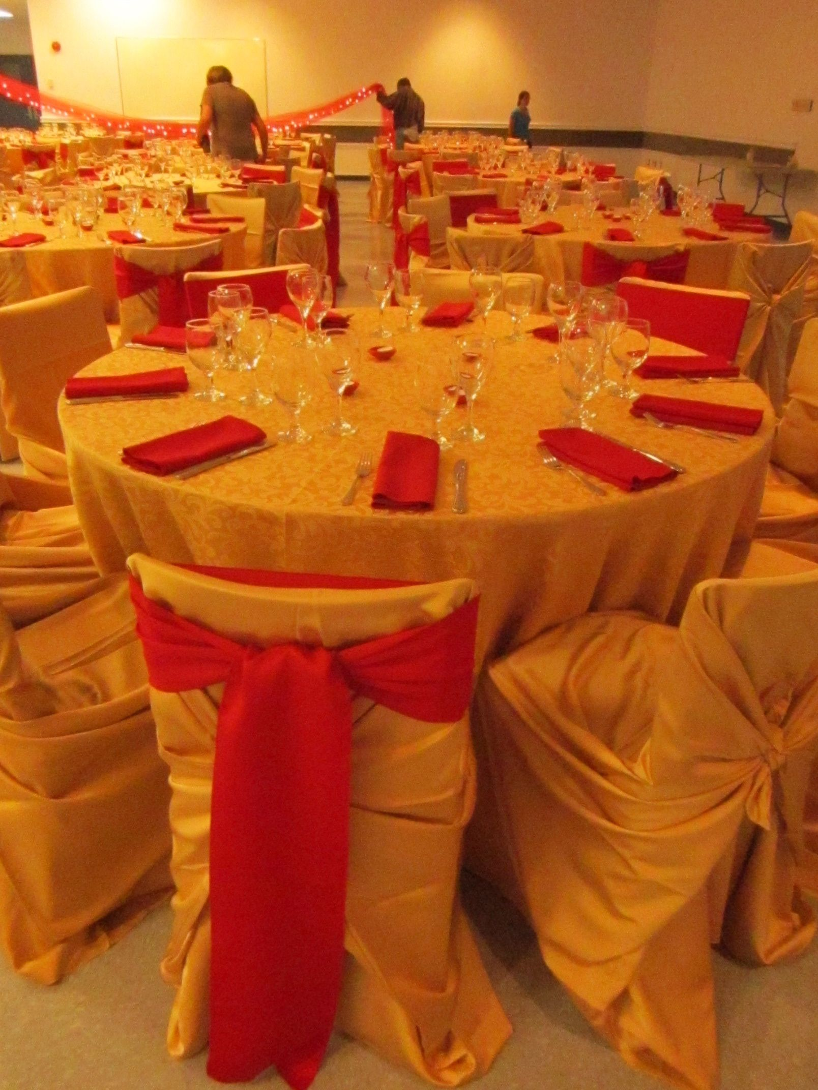 Dramatic gold linen and chair covers with red napkins and sashes.