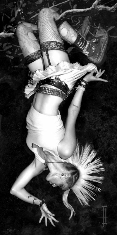 Fun, female punk upside down in a tree with a mohawk, skirt, and ripped fishnets