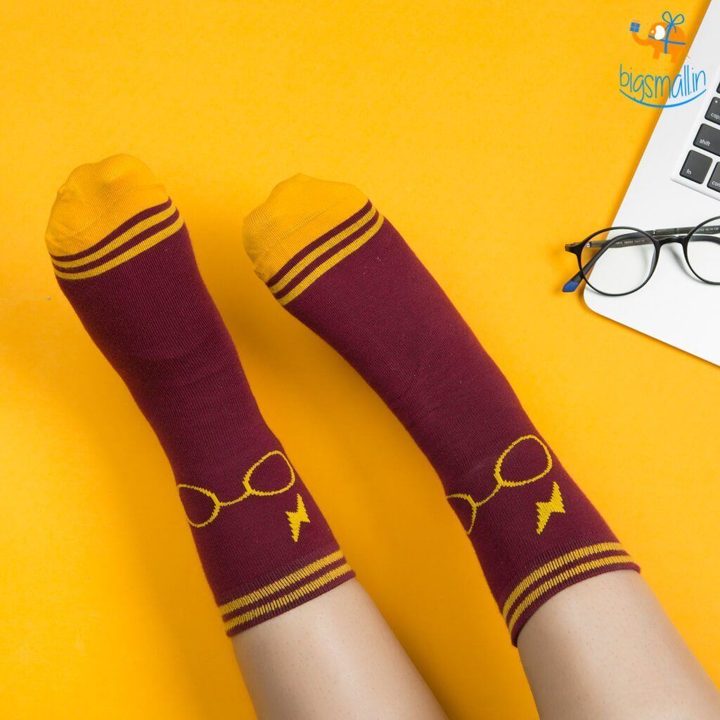 """We must make the choice between what is right and what is easy A wise man — Hogwarts headmaster Albus Dumbledore — once said that """"One can never have enough socks."""" And this is especially true when the socks in question are inspired by the Harry Potter series! That's why we conjured up something magical for Christmas. With the classic Gryffindor color scheme one is bound to teleport to the magical realm of Hogwarts. Talk about a perfect gift for basically everyone, but especially for the sock-lover (like Dobby the house elf) in your life. These unisex socks are hand knit with love from long lasting combed cotton and are available in free size. A well designed pedantry detailed socks to your casual outfit or a quirky add on to your formal suit. Your Gringotts vault will thank you for finding such an affordable gift option. Official LicensedHarry Pottermerchandise Harry Potter-themed pair of socks Lose yourself in the magical world of Harry Potter Official harry Potter merchandise Pair of socks with Harry Potter silhouette inscribed in them Extremely comfortable Great gift for all the Potterheads out there Size: Free size Unisex socks Classic Harry Potter maroon and gold color scheme Fabric: Soft-Combed Cotton with Stretch Spandex Material: 85% cotton, 13% Polyamide and 2% Elastane Package Includes: 1 xOfficial Harry Potter socks Category: Official Harry Potter merchandise Subcategory: Winter gifts"""