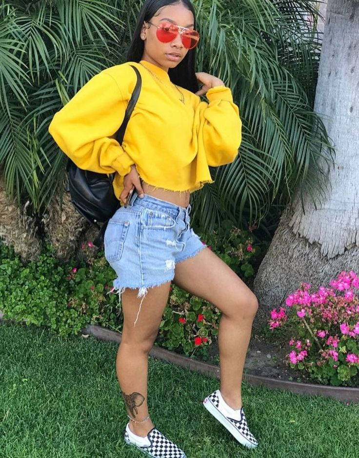 Instagram Baddie wearing distressed jean shorts black and white checkered Vans sneakers and a ...