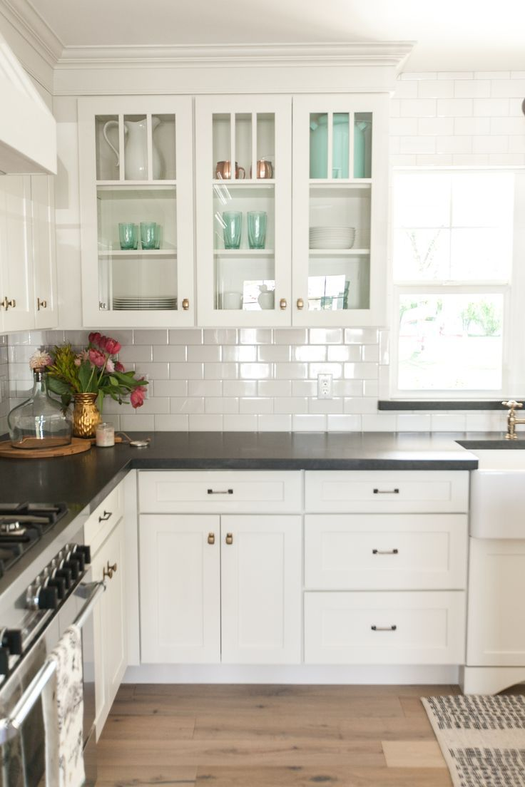 White kitchen cabinets, black countertops and white subway