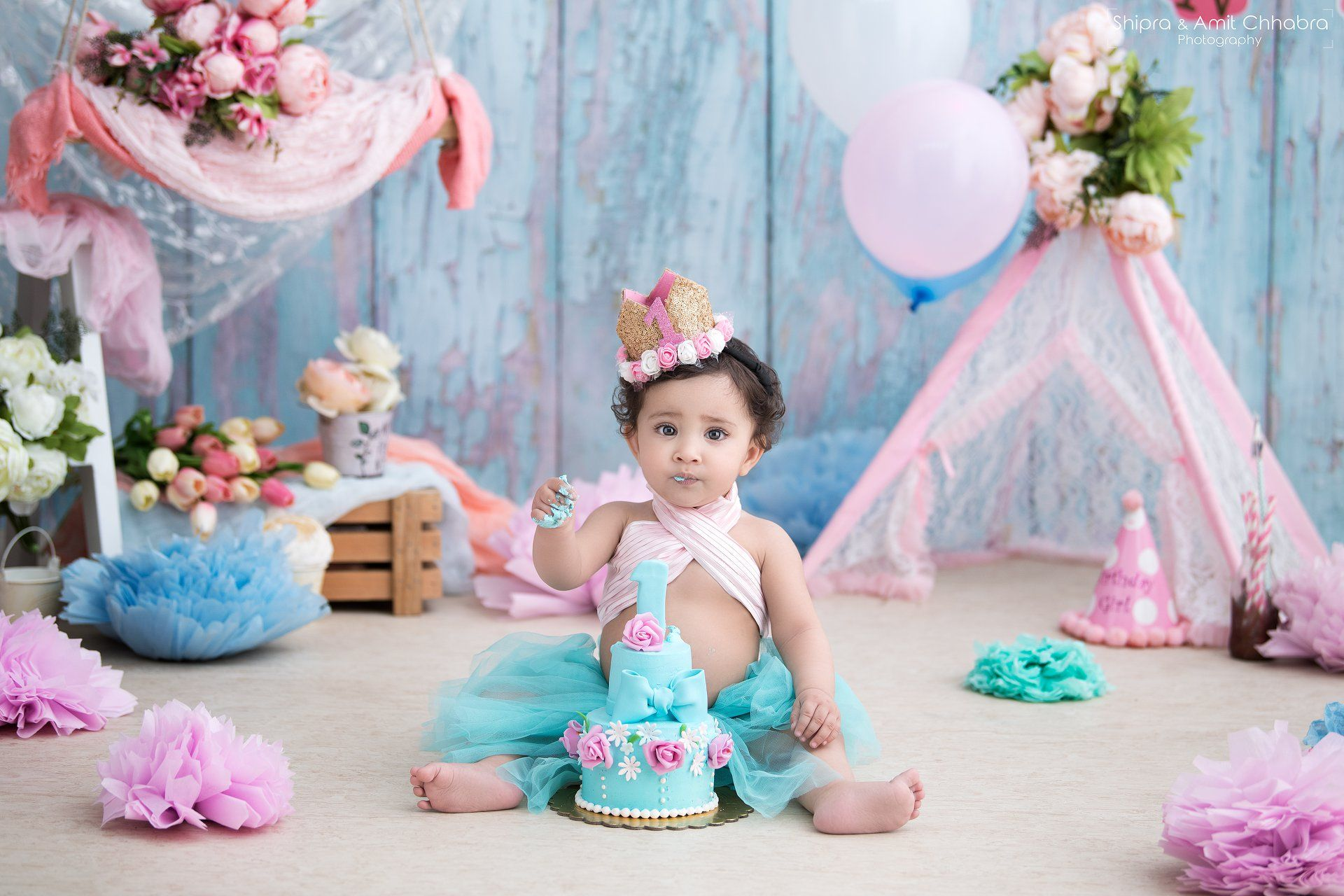 First birthday shoot cake smash photo shoot green floral cake 2 tier cakes tutu dress teepee set shipra amit chhabra photography