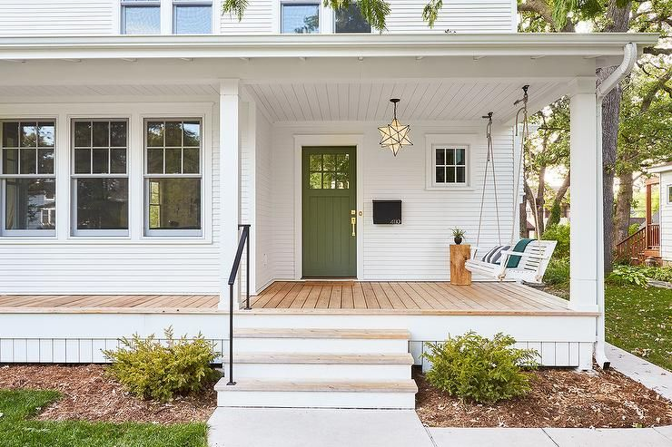 An Olive Green Front Door Accents A White Home Fitted With White Siding And A Moravian Star Pendant Hung From A Green Front Doors Front Door Colors Door Color