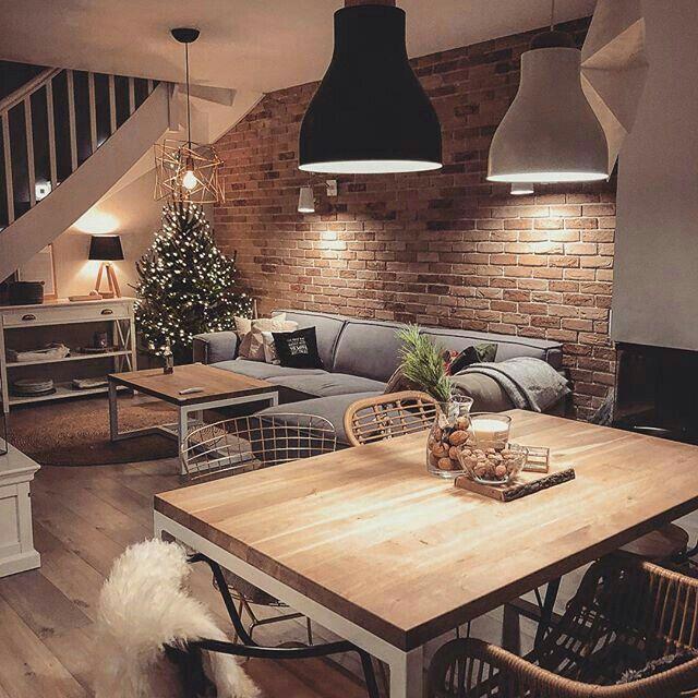 Parede tijolinho, luz amarela, mesa madeira, pendente mesa, árvores Natal simples, escada caracol, pelego, pelo, sofá cinza, madeira e branco #saloncocooning
