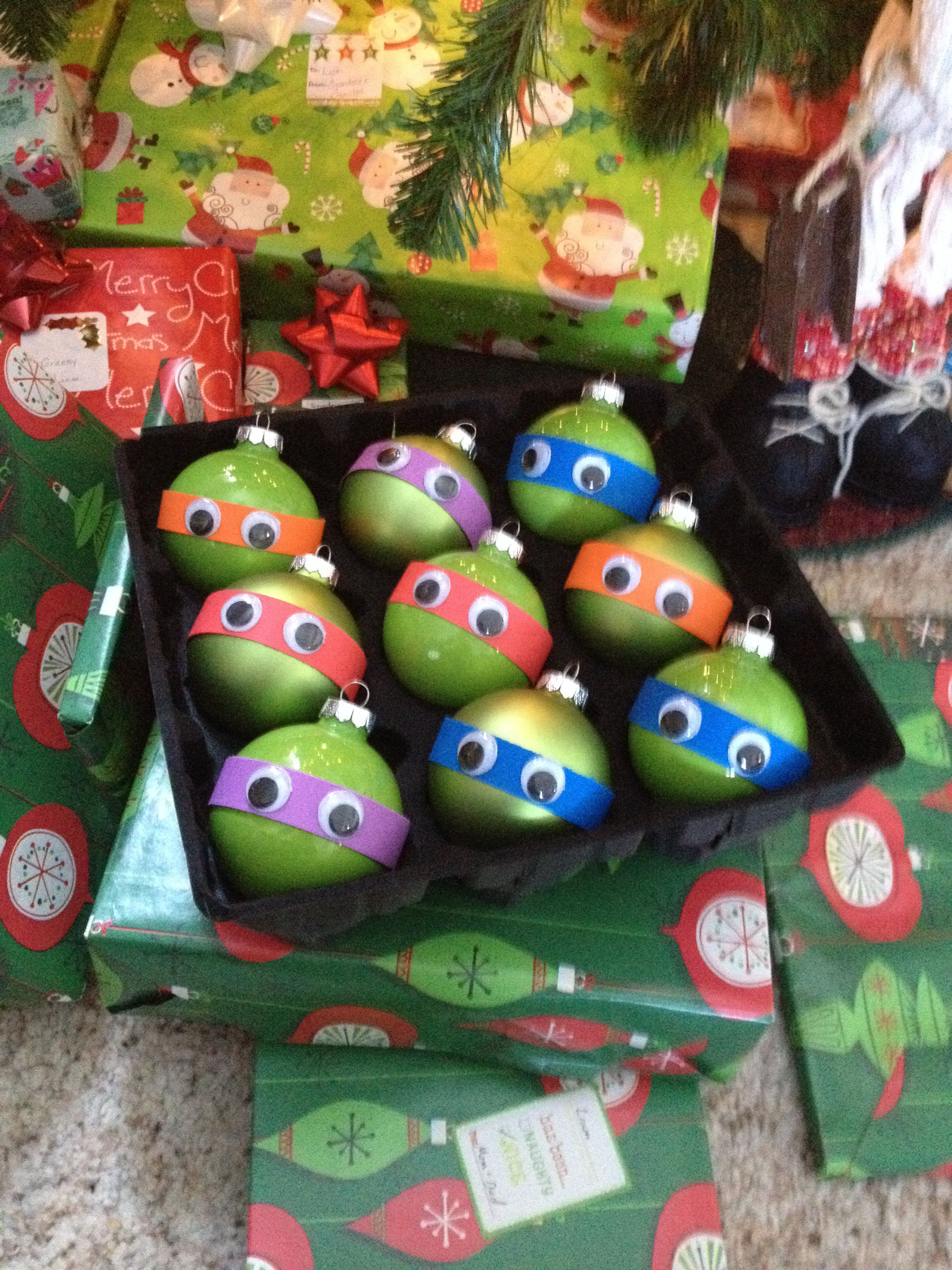 Easy TMNT ornaments. Green glass bulbs, construction  paper masks connected with hot glue, and sticker eyes.